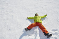 Young boy making snow angel in snow - ISF09880