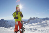 Portrait of young boy in ski wear, holding skis - ISF09889