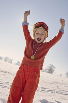 Young boy with medal around neck, celebrating with arms raised - ISF10015
