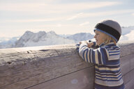 Young boy looking over wooden barrier at mountain view - ISF10027