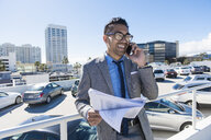 Young businessman on city rooftop car park smiling whilst talking on smartphone - ISF10054