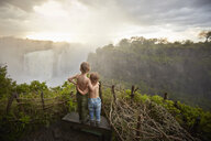 Two young boys standing on ledge admiring the view, rear view, Victoria Falls, Livingstone, Zimbabwe - ISF10093