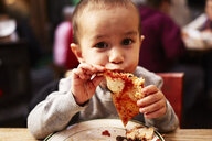 Boy eating pizza in restaurant - ISF10168