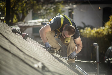 Solar panel installation worker working on roof of house - ISF10225