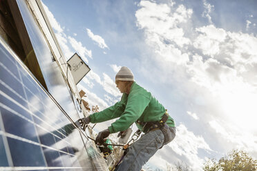 Construction crew member installing a solar panel on a house - ISF10228