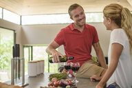 Couple preparing food and pouring red wine in kitchen - ISF10354