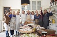 Portrait confident active senior friends and chef taking pizza cooking class - CAIF20707