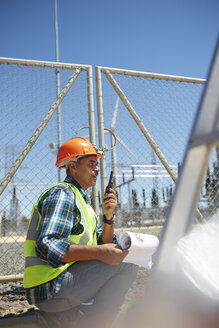 Engineer with walkie-talkie at sunny power plant - CAIF20767