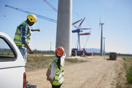 Engineers on dirt road at wind turbine power plant - CAIF20773