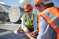 Engineers with clipboard examining solar panel at sunny power plant - CAIF20779