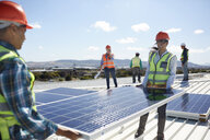 Engineers lifting solar panel at sunny power plant - CAIF20785