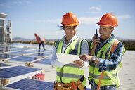 Engineers using walkie-talkie and digital tablet at solar power plant - CAIF20797