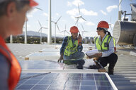 Engineers examining solar panels at alternative energy power plant - CAIF20800