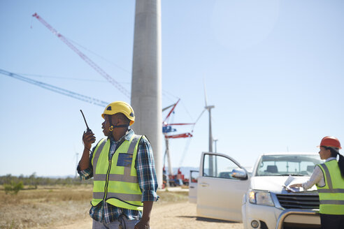 Male engineer with walkie-talkie at sunny wind turbine power plant - CAIF20803