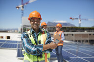 Portrait confident engineer installing solar panels on sunny rooftop - CAIF20806