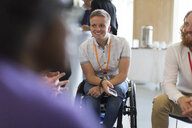 Smiling woman in wheelchair talking to colleagues in conference - CAIF20830