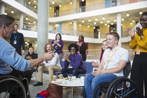 Colleagues clapping for speaker in wheelchair at conference - CAIF20923