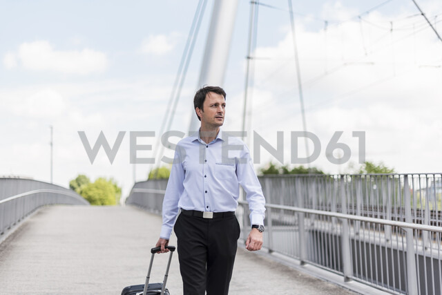 Businessman with rolling suitcase crossing a bridge - DIGF04680