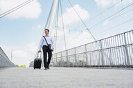 Businessman with rolling suitcase crossing a bridge - DIGF04683