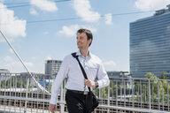 Smiling businessman walking on a bridge - DIGF04686