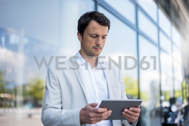Businessman using tablet in the city - DIGF04698