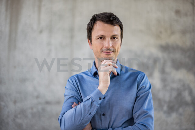 Portrait of confident businessman in front of concrete wall - DIGF04710
