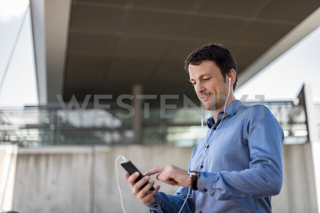 Smiling businessman with cell phone and earphones outdoors - DIGF04713