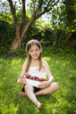 Portrait of smiling little girl sitting on meadow with bowl of strawberries - LVF07099