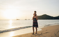 Thailand, Krabi, Koh Lanta, Mother with little daughter on her shoulders on the beach at sunset - GEMF02080