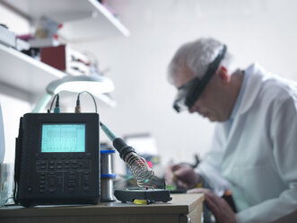 Engineer soldering prototype circuit board with oscilloscope in foreground - CUF32394