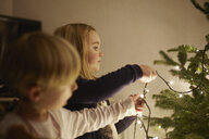 Young brother and sister putting up christmas lights - CUF32436