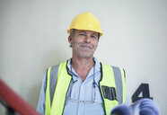 Portrait of senior male surveyor holding blueprints - CUF32526