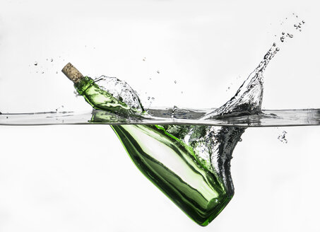 Surface level view of green bottle splashing into clear water - CUF32556