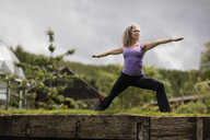 Mature woman practicing warrior pose in eco lodge garden - CUF32622