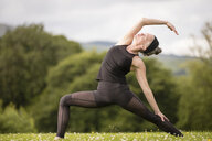 Mature woman practicing yoga pose in field - CUF32628