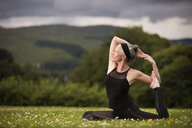 Mature woman doing splits practicing yoga in field - CUF32631