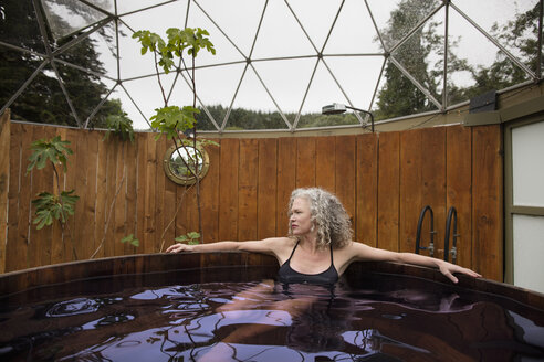 Mature woman relaxing in hot tub at eco retreat - CUF32637