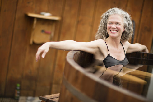 Smiling mature woman in hot tub at eco retreat - CUF32640