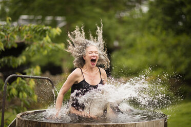Mature woman splashing into fresh cold water tub at eco retreat - CUF32643