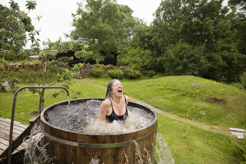 Mature woman splashing in fresh cold water tub at eco retreat - CUF32646