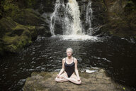 Mature woman practicing lotus pose in front of waterfall - CUF32649