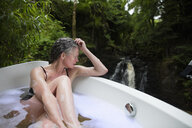 Mature woman in bubble bath in front of waterfall at eco retreat - CUF32652