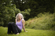 Mature woman taking a break from yoga practice in field - CUF32655