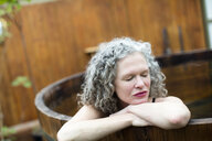 Mature woman resting on hands in hot tub at eco retreat - CUF32661