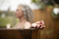 Mature woman meditating in hot tub at eco retreat - CUF32664