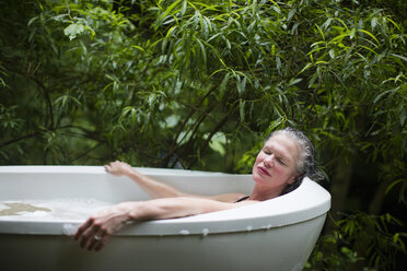 Mature woman relaxing in garden bubble bath at  eco retreat - CUF32667