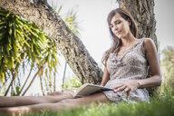 Mid adult woman reading book under palm tree in holiday home garden, Capoterra, Sardinia, Italy - CUF32811