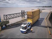 Elevated view of truck and shipping container on ramp to ship - CUF32817