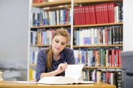 Young female student reading textbook at library desk - CUF32990