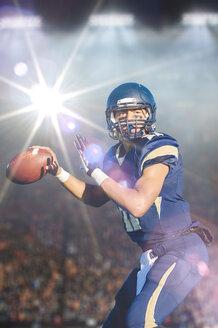 Teenage american footballer holding up ball in stadium - ISF10445